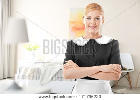 Chambermaid standing on bedroom background