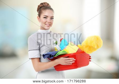 Chambermaid with cleaning equipment on blurred background