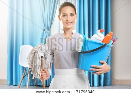 Chambermaid with cleaning equipment on living room background