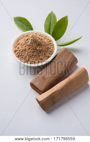 Chandan or sandalwood powder with traditional mortar, sandalwood sticks, perfume or oil and green leaves. selective focus