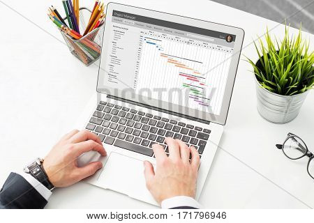 Businessman using project management software on compter