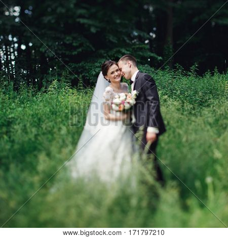Happy Cute Newlywed Couple Hug & Kiss In Park Outdoors