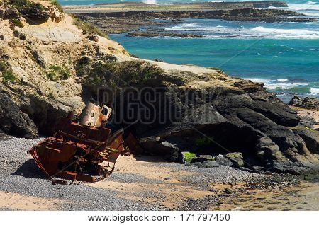 Wrecked old ruined rusted and almost destroyed pusher boat on the beach against the rocks with the ocean waves behind. Milfontes Portugal.