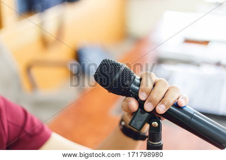 Man with Microphone in concert hall or conference room with defocused bokeh lights in background