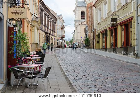 VILNIUS LITHUANIA - JULY 10 2015: Unknown people go along street in Old Town Vilnius Lithuania