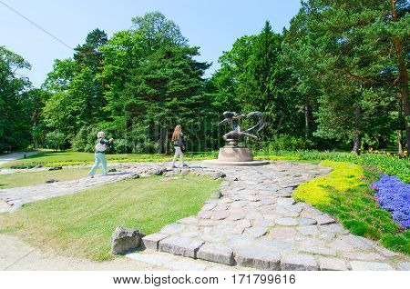 PALANGA LITHUANIA - JULY 12 2015: Unidentified tourists are near sculpture