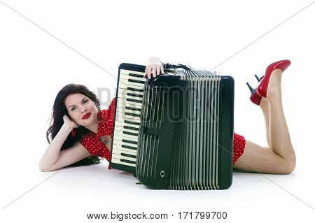 pretty bruntette woman in red lies with accordion on floor of studio with white background
