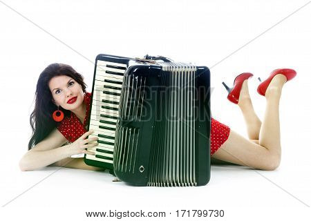 pretty woman in red lies with accordion on floor of studio with white background