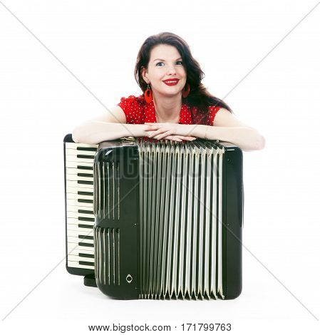 pretty woman in red leans on accordion on floor of studio with white background and smiles