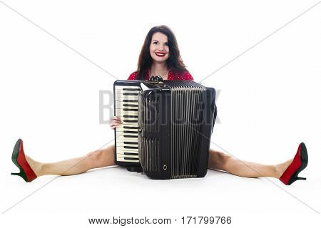 pretty woman in red sits with accordion on floor of studio with white background