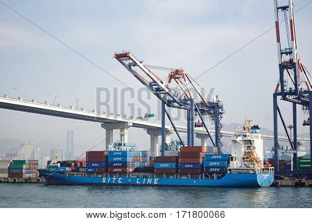 Busan South Korea - March 22th 2016: Busan container truck SITC Fangcheng under loading against sea cranes and the bridge.