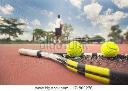Tennis racket and ball and sky background