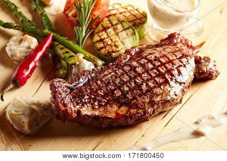 Beef Steak - BBQ Strip Steak (Grilled Beef Strip Loin Steak) with Roast Vegetables and White Sauce.