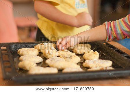 Little girl puts hand made biscuits on baking tray in Waldorf kindergarten