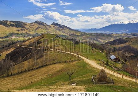 Rural scenery with traditional houses and haystock in Magura village, Brasov, Transylvania region, Romania.