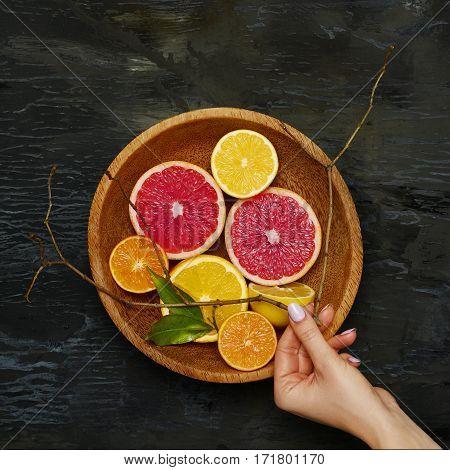 Grapefruit citrus fruit halves on wooden plate background.