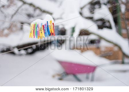 plastic varicoloured clothes pins on the rope in winter snowy day with snowflakes