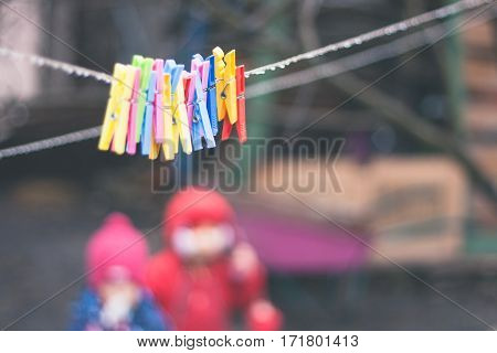 plastic varicoloured clothes pins on the rope in spring rainy day with water drops and two little girls unfocused