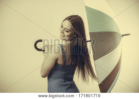 Woman fashion summer attractive girl wearing dress standing under umbrella toned image. Positive smiling female model. Forecasting and weather season concept