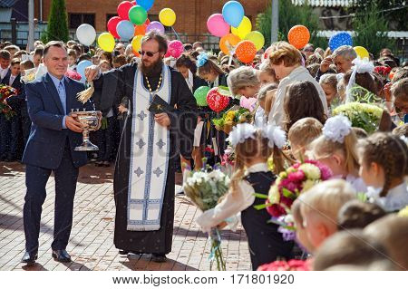 BALASHIKHA/ RUSSIA - SEPTEMBER 1. The priest sprinkles the crowd with holy water at the celebration of the beginning of the new school year on September 1, 2016 in city Balashikha, Moscow region, Russia.