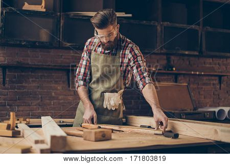 Young Stylish Craftsman With Glasses And Hairstyle Holding Measuring Tape Near Blank At Tabletop In