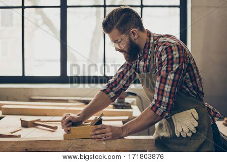 Side View Photo Of Stylish Handsome Cabinetmaker Work With Jointer And Plank. Man With Brutal Hairst