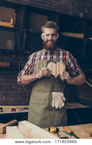 Happy Handsome Joiner In Love Holding And Showing Wooden Heart Near Tabletop With Tools.  Stylish Yo