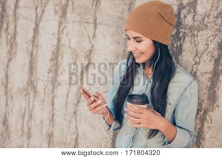 Portrait Of Happy Trendy  Woman With Cup Of Coffee Listening Music On  Phone