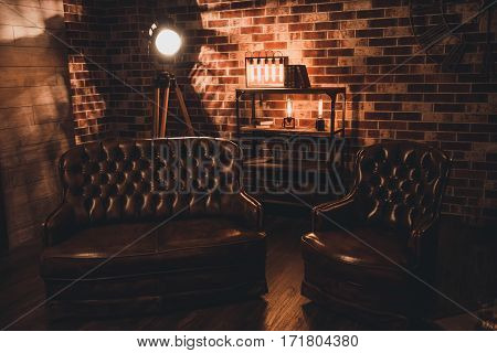 Loft interior. Leather couch and armchair in a dark room