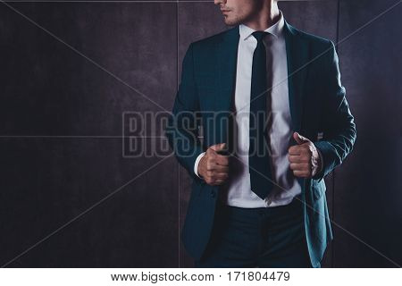 Close Up Of Young Businessman Touching His Black Suit