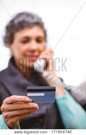 Close-up of mature woman holding payment card while talking on telephone at home