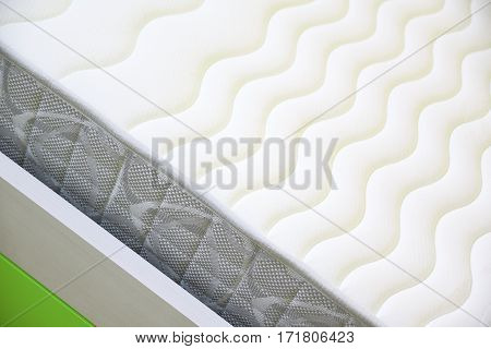 Textured mattress detail on a bed. Empty copy space for Editor's text.