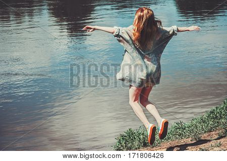 Happy Woman jumping up flying levitation river landscape on background. Lifestyle Travel emotions.