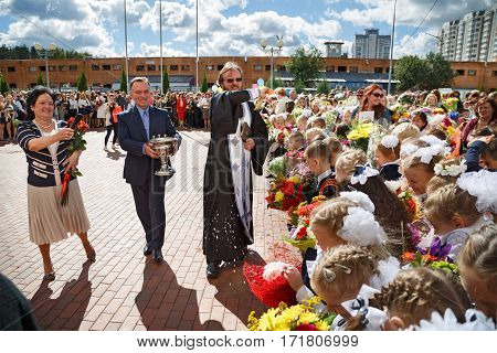 BALASHIKHA/ RUSSIA - SEPTEMBER, 1, 2016: The priest sprinkles the crowd with holy water at the celebration of the beginning of the new school year on September 1, 2016 in Balashikha, Russia.