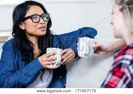 Close-up of young woman talking with female friend while drinking coffee at home