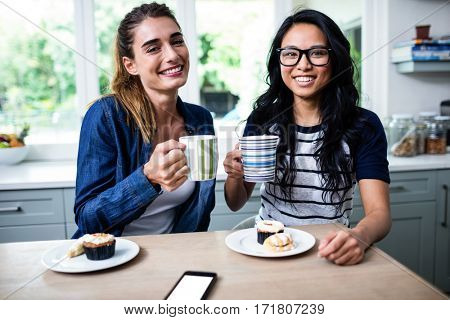 Portrait of happy young female friends holding coffee mug during breakfast at home