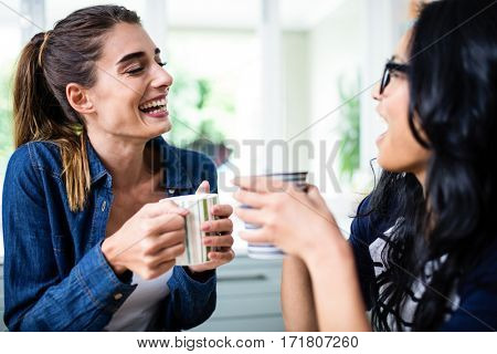 Close-up of beautiful female friends laughing while drinking coffee at home