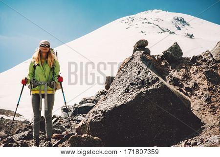 Young Woman traveler with backpack hiking in mountains Travel Lifestyle adventure concept active vacations outdoor mountaineering sport success Elbrus mountain on background