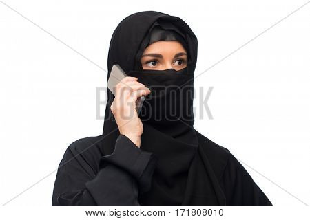 technology, communication and people concept - muslim woman in hijab calling on smartphone over white background