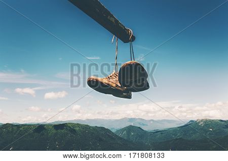 Shoes trekking boots hanging over mountains aerial landscape Travel Lifestyle adventure vacations concept blue sky and clouds on background