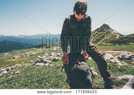 Man traveler packing backpack hiking in mountains Travel Lifestyle concept adventure active summer vacations outdoor