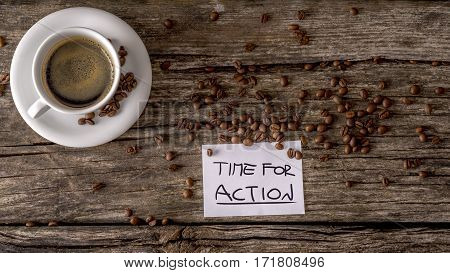 Cup of coffee on saucer and coffee beans over old rough wooden surface and white sheet of paper with Time For Action sign. Copy space.