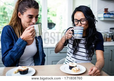 Close-up of young female friends drinking coffee at table in house