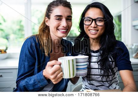 Portrait of cheerful young female friends holding coffee mug at home