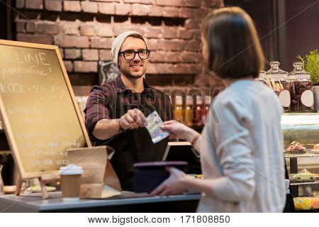 small business, payment, people and service concept - happy barman and woman paying money at cafe