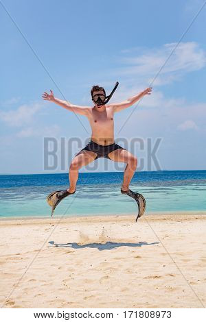 Funny man jumping in flippers and mask. Holiday vacation on a tropical beach at Maldives Islands.