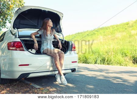 Relaxed happy woman sit at car rear on summer road trip travel.