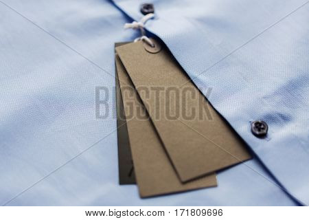 clothes, fashion, formal wear, shopping and objects concept - close up of shirt with price tag