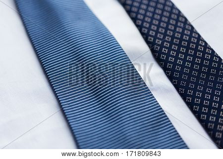 clothing, formal wear, fashion and objects concept - close up of shirt and blue patterned ties