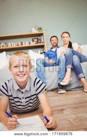Portrait of happy boy drawing on book while parents looking at him from sofa in living room